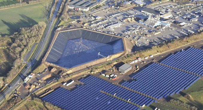 Solarthemriekraftwerk der VOJENS FJERNVARMEVÆRK im dänischen Vojens mit insgesamt 70.000 Quadratmetern Kollektorfläche und 50 MW Leistung. Links ist ein 14 Meter tiefer Wärmespeichr zu sehen, der Warmwasser für den Winter speichert. Foto: Arcon Sunmark