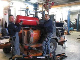 Sékou Timplan (rechts) und ein Mitarbeiter montieren in ihrer Leipziger Werkstatt einen 100-Liter-Autogas-Tank. Die Vorrichtungen dafür fertigten sie selbst. Foto: Urbansky