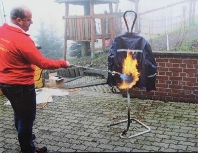 Die Tkw-Fahrer-Jacke von Walther Arbeitsschutz hält selbst einer Beflammung mit Dachbrenner stand (Bild oben), während ein normales T-Shirt schon von einem handelsüblichen Unkrautabbrenner abgefackelt wird (Bild unten). Fotos: HHManz / Brennstoffspiegel