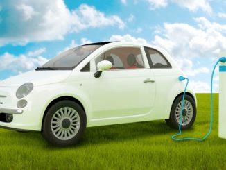 Elektroauto auf grüner Wiese an Stromsäule