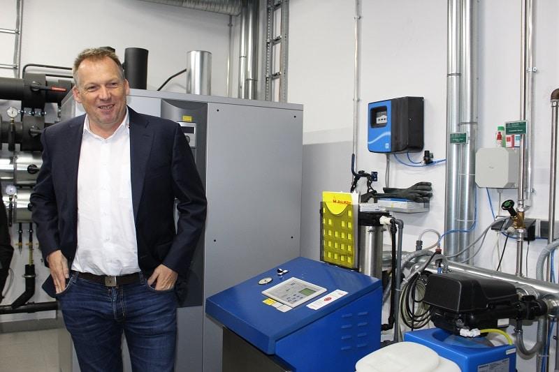 Firmenchef Andreas Müller vor der Steuereinrichtung der Anlage und dem Stromspeicher (hinten).