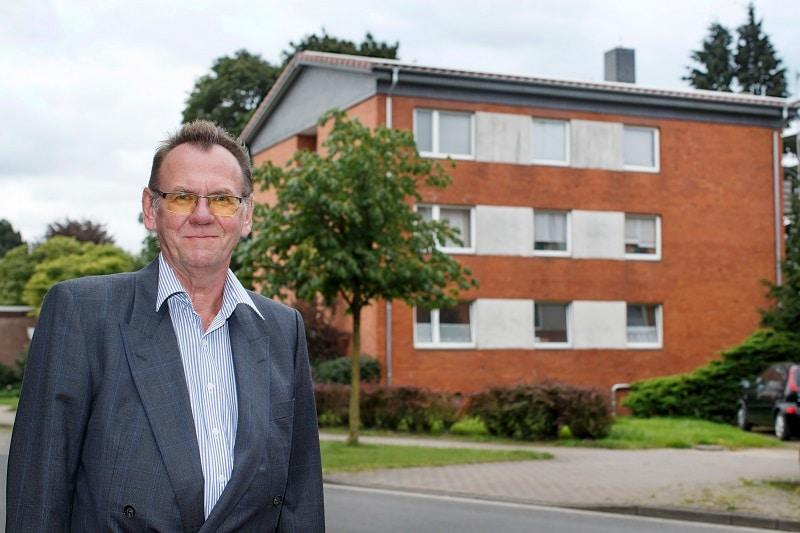 Martin Henne vor dem von ihm energetisch sanierten 6-Familien-Haus. Die Versorgung übernehmen weitestgehend zwei BHKW. Fotos: E3/DC / Andreas Burmann
