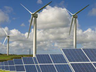 Grünes Feld mit Windturbinen und Solaranlagen unter bewölktem und blauem Himmel
