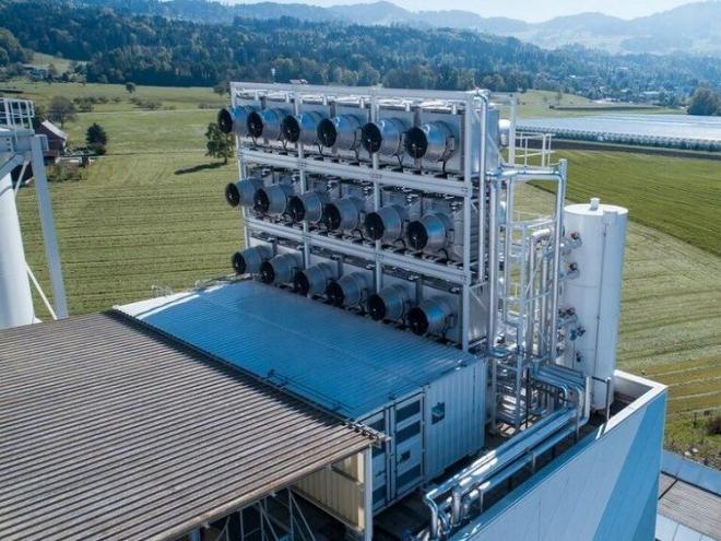 Die DAC-Anlage im Vordergrund und das mit Kohlendioxid gespeiste Gewächshaus im Hintergrund. Climeworks / Julia Dunlop